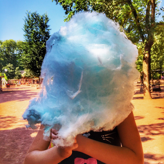 """Little girl with blue fairy floss."" stock image"