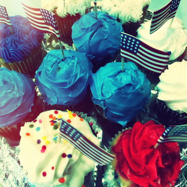 """Cupcakes with red, white and blue frosting and miniature American flags."" stock image"