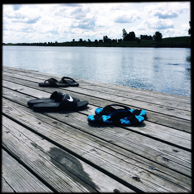 """""""Three pair of sandals that were left behind by water sport loving owners."""" stock image"""