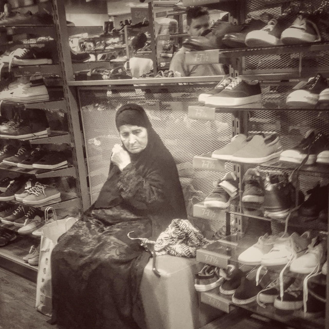 """Woman in hijab sitting in a shoe shop"" stock image"