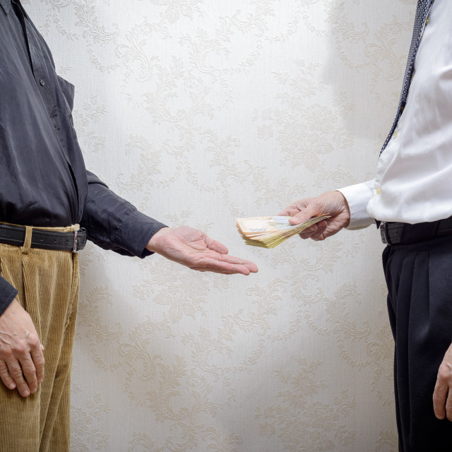 """""""Man Paying a Hryvnia Bribe to a Corupted Nan Accepting It"""" stock image"""