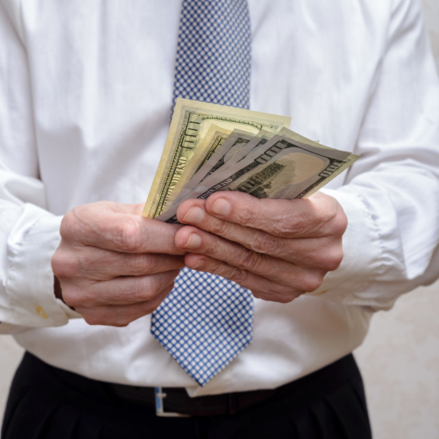 """Businessman, or politician, counting a Dollar banknotes bribe fo"" stock image"