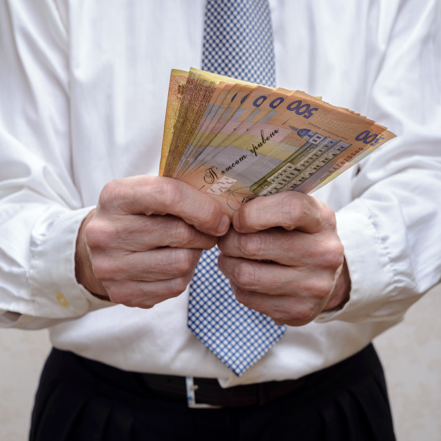 """Businessman, or politician, counting a Hryvnia banknotes bribe f"" stock image"