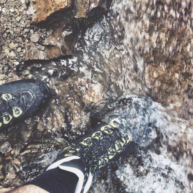 """""""Hiking boots walking into the fresh water of a mountain stream or creek"""" stock image"""