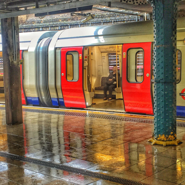 """Alone on the tube. Whitechapel station, slightly illuminated with light on water, after the rain. London, U.K."" stock image"