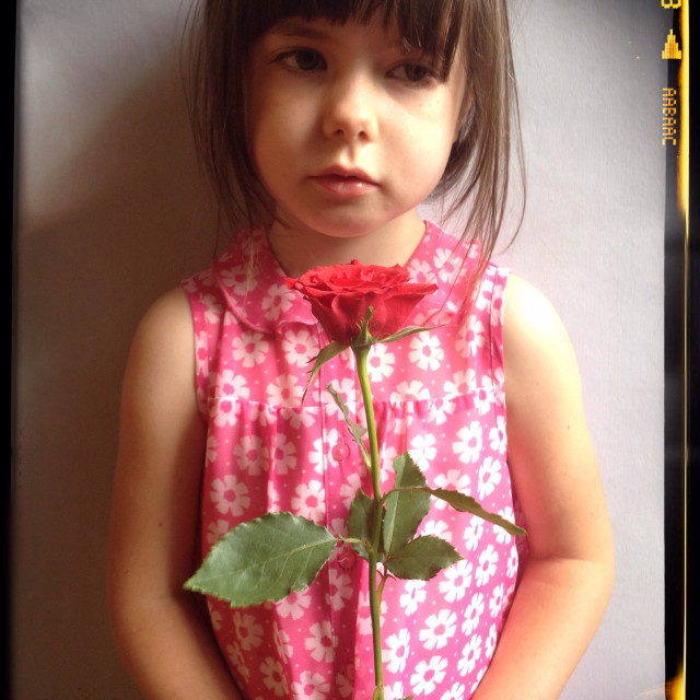 """Unhappy young girl holding a rose"" stock image"