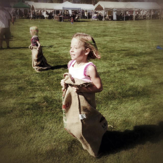 """""""Girls participate in a sack race at a fair."""" stock image"""