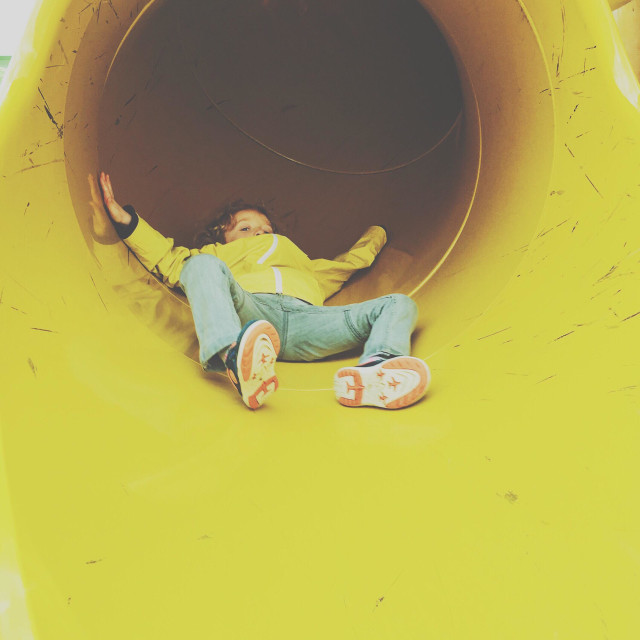 """Boy coming down slide"" stock image"