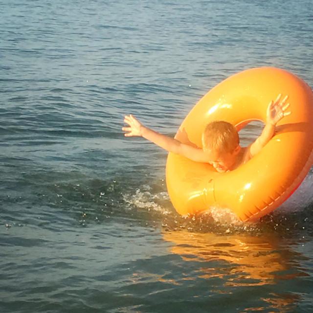 """Boy jumping through a tube in the lake, Georgian Bay,Ontario, Canada"" stock image"