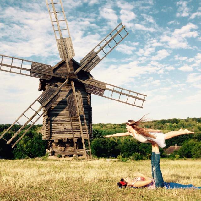 """Acro yoga near windmill"" stock image"