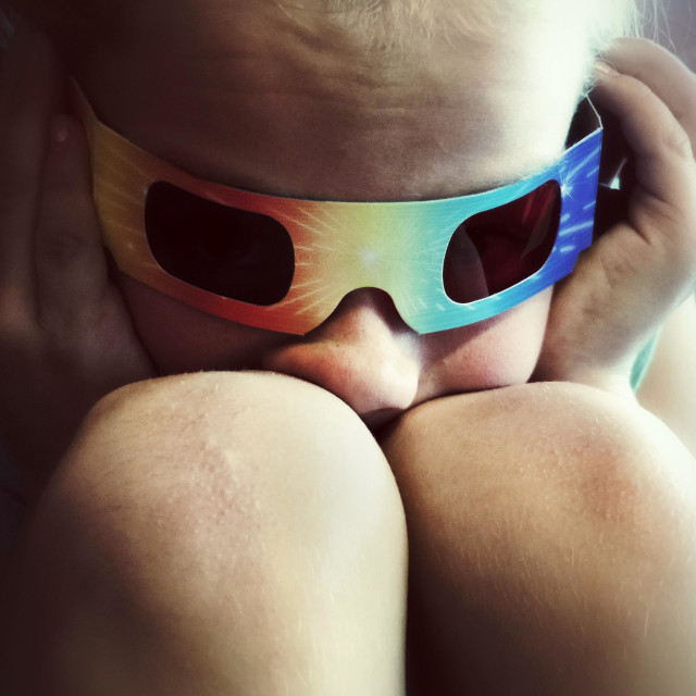 """A child wearing 3D glasses has its nose squished between its knees."" stock image"