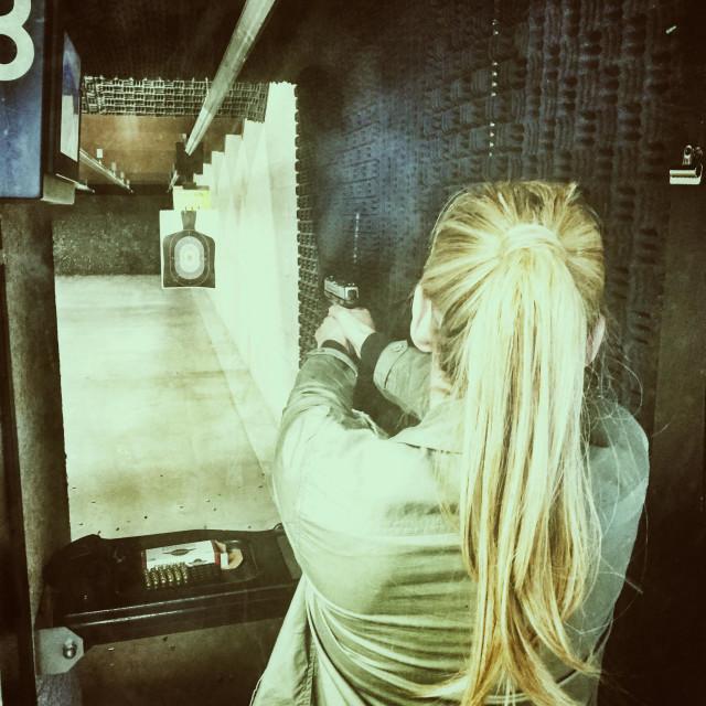 """Woman shooting her weapon at indoor range."" stock image"