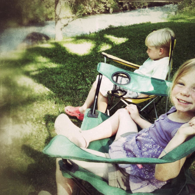 """""""Two children sit in camping chairs beside a creek."""" stock image"""