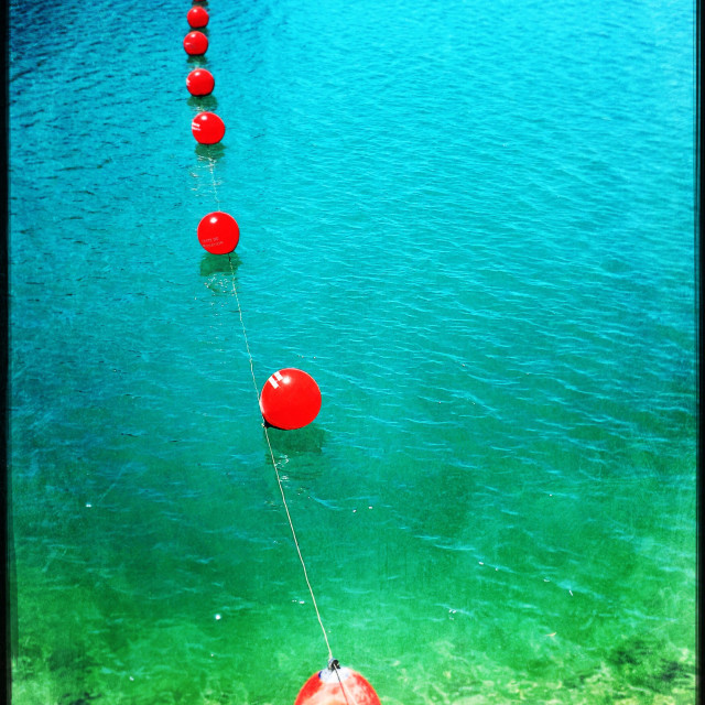 """Colourful red buoy's floating on turquoise freshwater lake in Andalusia Spain"" stock image"