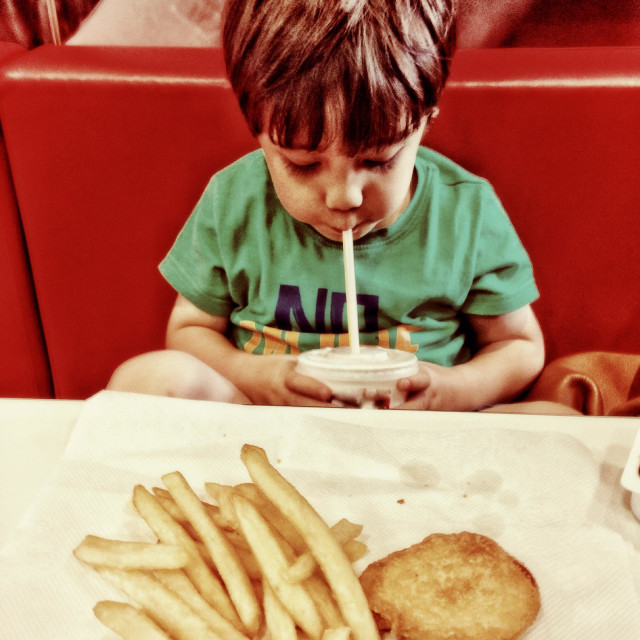 """A young boy eating in a fast food restaurant/"" stock image"