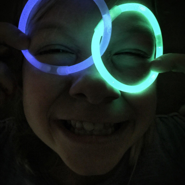 """A child makes a silly grin pretending to wear glow sticks as glasses."" stock image"