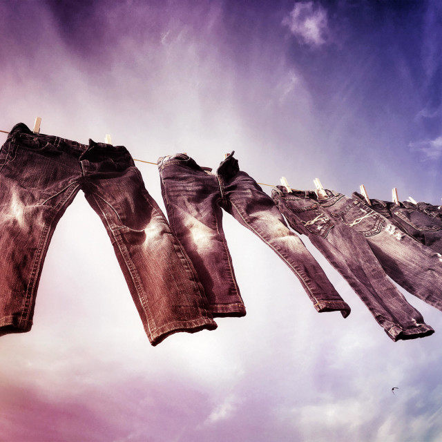 """""""Childrens trousers drying on a clothes line after laundry."""" stock image"""