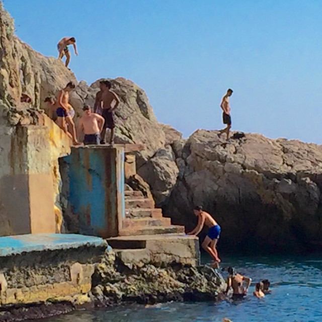 """""""Boys diving from the rocks in Nice, France"""" stock image"""