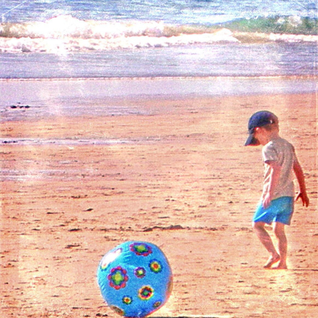 """""""...rough sea, great ball and tough little boy..."""" stock image"""
