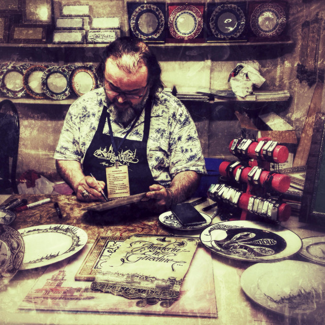 """Artisan making calligraphy on a dish during Ramadan events in Sultanahmet"" stock image"