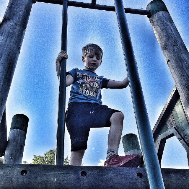 """Boy on a climbing frame feeling nervous"" stock image"