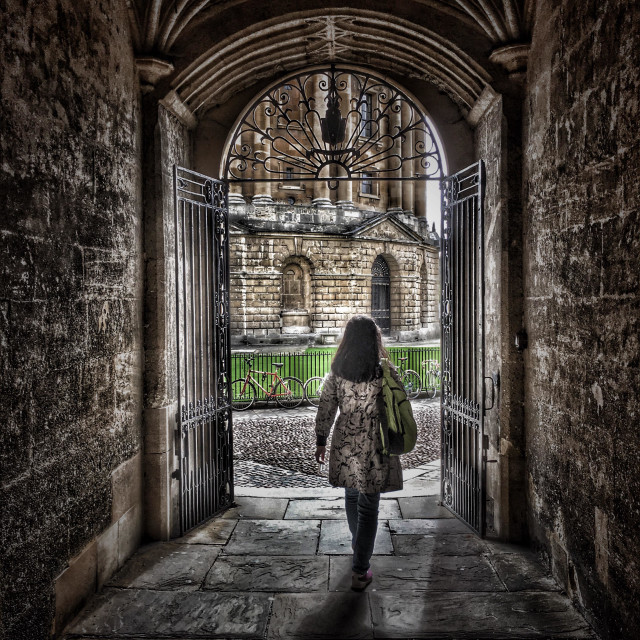 """Female leaving the Bodleian Library, walking towards the Radcliffe Camera, University of Oxford, England"" stock image"