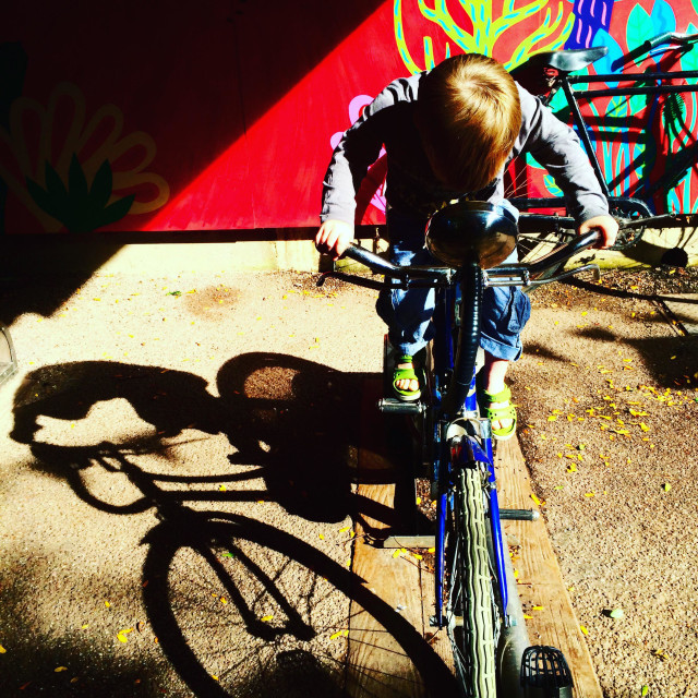 """Boy toddler rides a static bike at London zoo"" stock image"