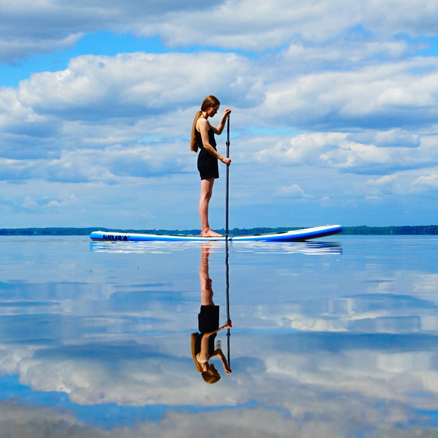 """""""a girl on a paddle board in a lake"""" stock image"""