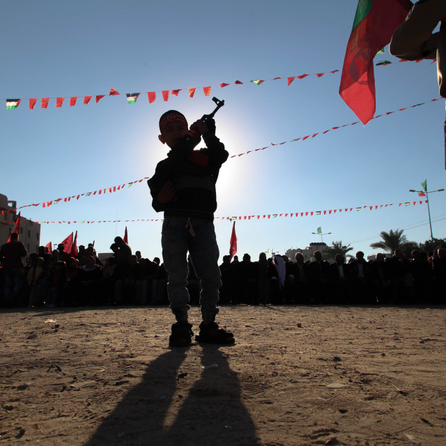 """Palestinian boy carries gun during festival to mark the national event in northern Gaza"" stock image"