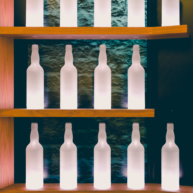 """""""Parallel wooden shelves with row of white alcohol bottles"""" stock image"""