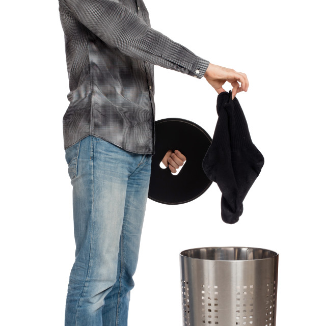"""""""Young man putting dirty socks in a laundry basket"""" stock image"""