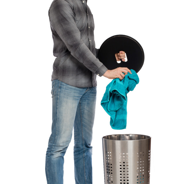 """""""Young man putting a dirty towel in a laundry basket"""" stock image"""