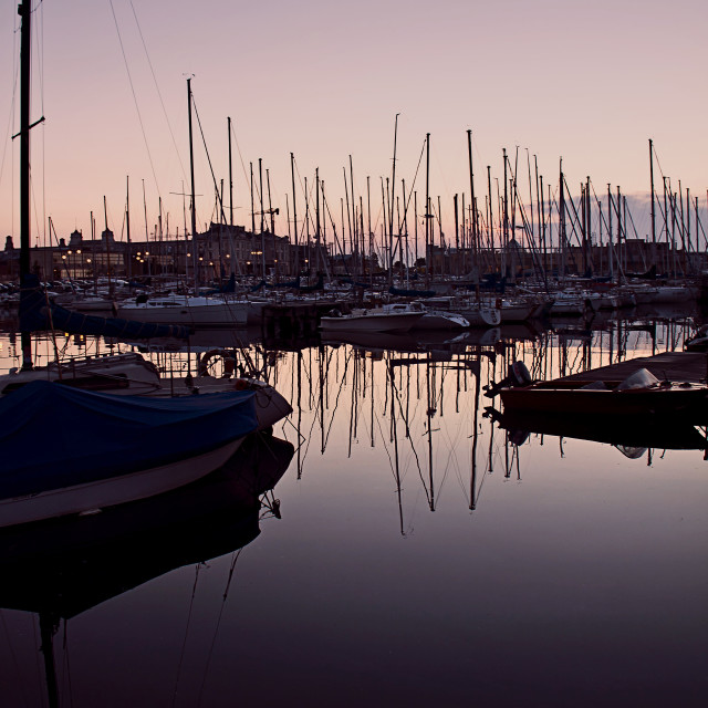 """""""Twilight on the harbor with calm waters and boat reflections"""" stock image"""