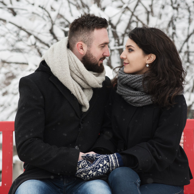 """""""couple sitting on red bench and looking at each other"""" stock image"""