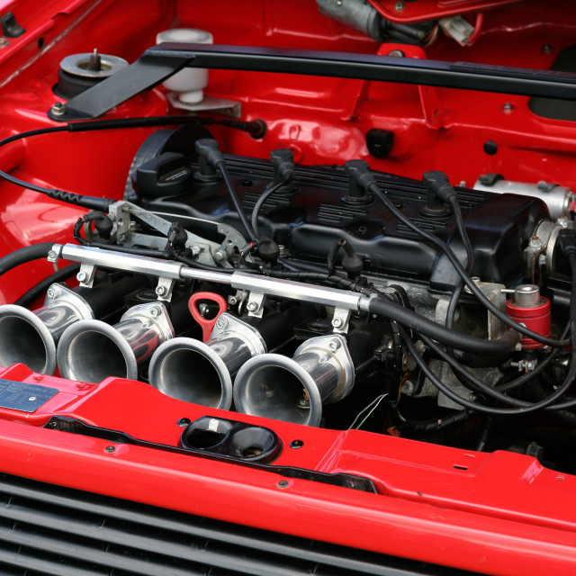 """Red car engine bay with Carb inlets"" stock image"