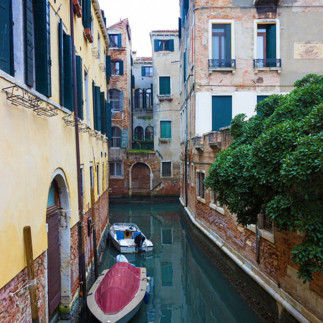 """Typical Venice canal with moored boats"" stock image"