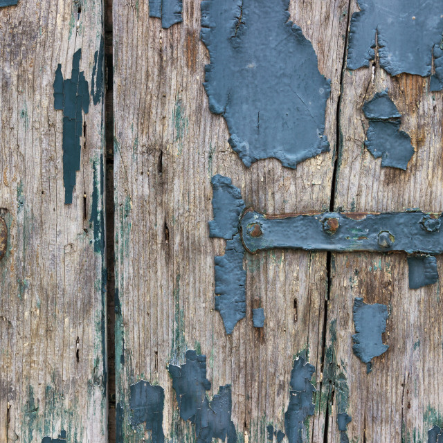 """Detail of a wooden window with blue peeling paint"" stock image"