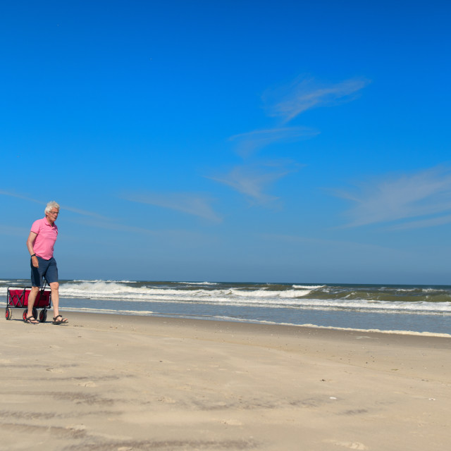 """Senior man walking with cart at the beach"" stock image"