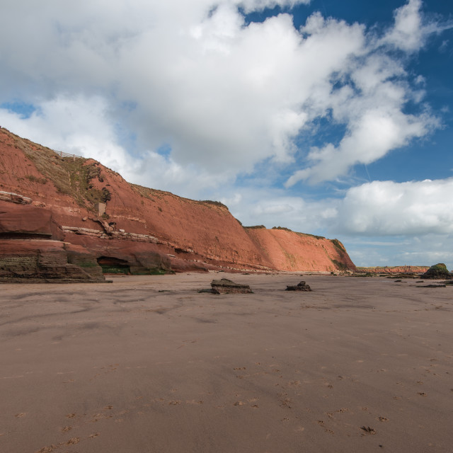 """""""Red rocky cliffs on Exmouth beach at low tide"""" stock image"""