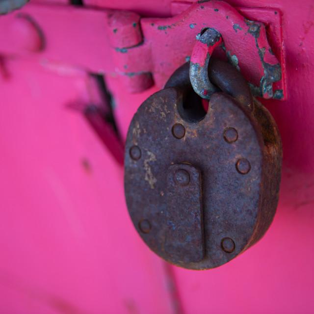 """Rusty padlock on pink background"" stock image"