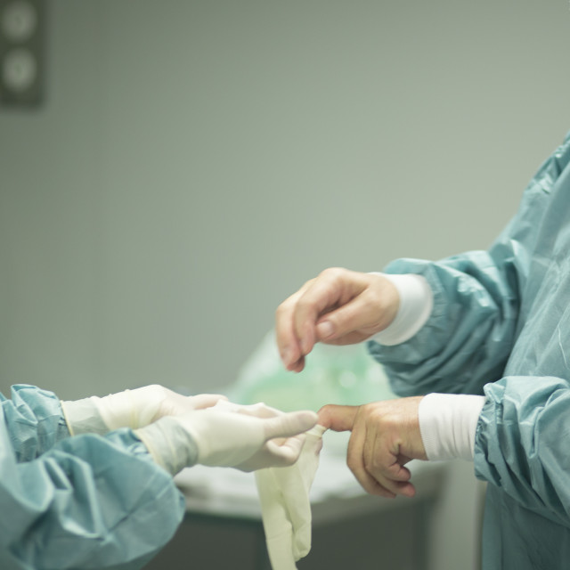 """Surgeon putting on gloves"" stock image"