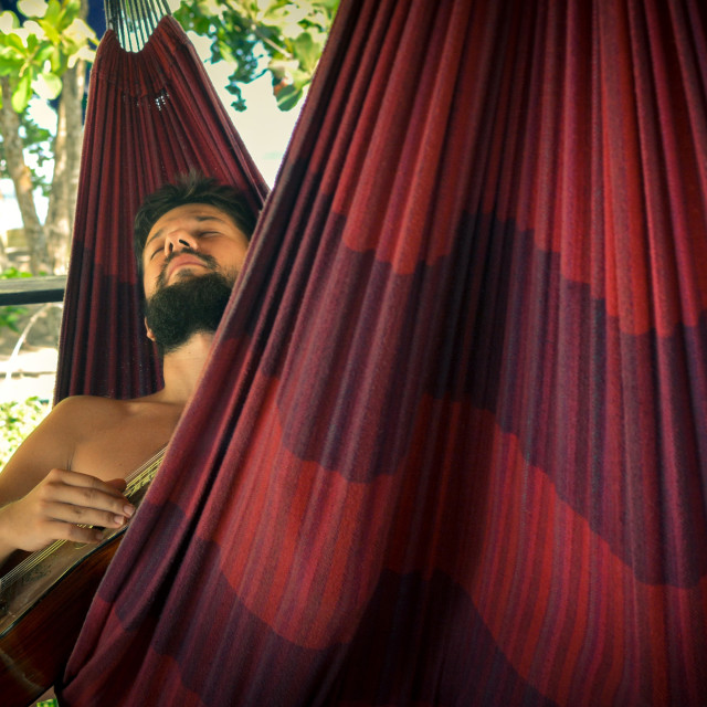 """man playing guitar in a hammock"" stock image"