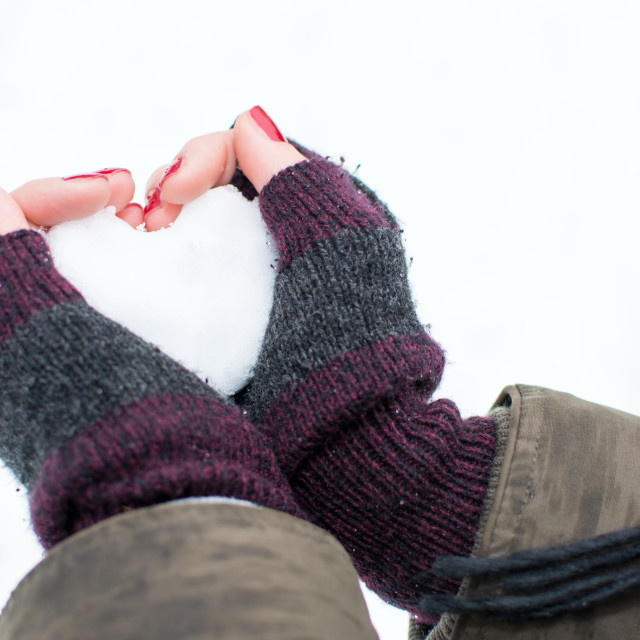 """""""Woman hands holding heart shaped snowball"""" stock image"""