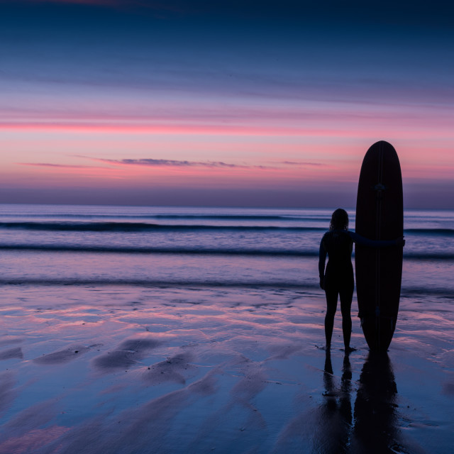 """Surfer silhouette on beach at sunset"" stock image"