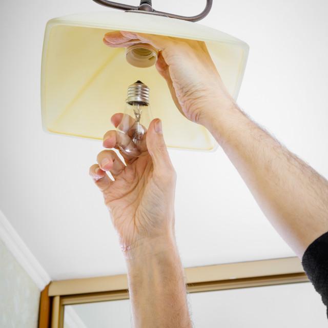 """Man Installing a Bulb"" stock image"