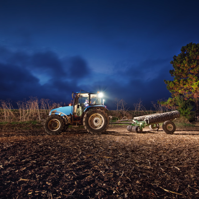 """Tractor preparing land with seedbed cultivator at night"" stock image"