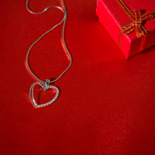 """""""Heart pendant on a red satin background"""" stock image"""