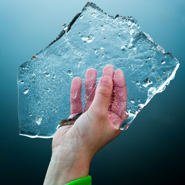 """""""Young boy keeps in cold hand slice of ice floe."""" stock image"""