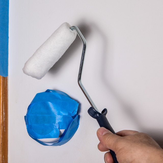 """Painters hand with roller and masking blue tape"" stock image"