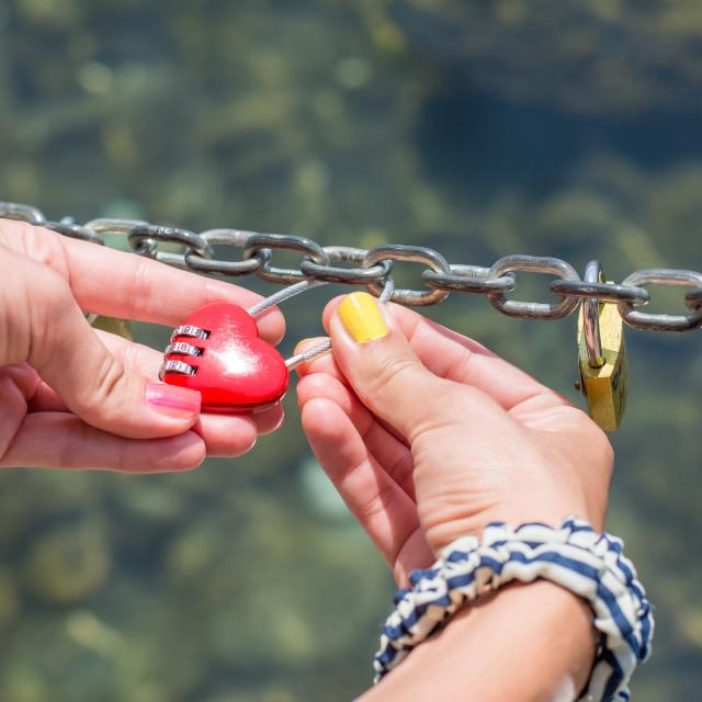 """Woman hand holding heart shaped padlock"" stock image"